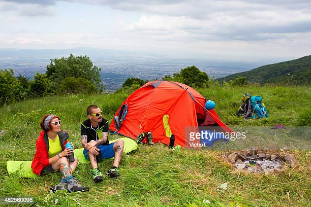 Young couple adventurers siting on their campsite