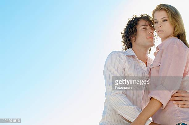 Young couple against clear sky (portrait, low angle view)