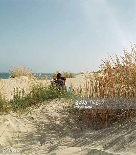 Young couple amongst  sand dunes, rear view