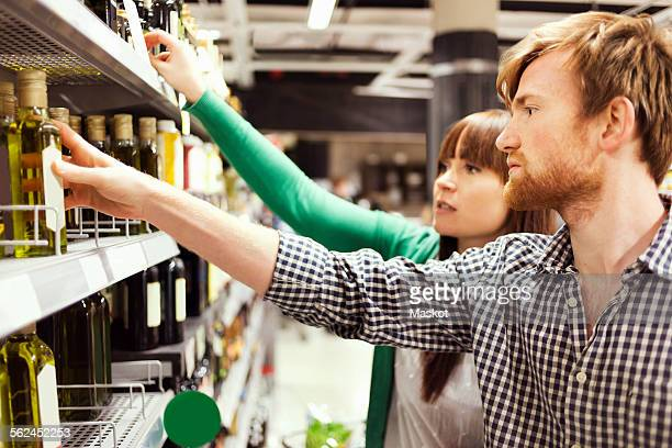 Young couple analyzing products in supermarket