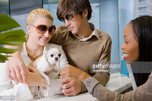 Young couple and a young woman looking at a puppy