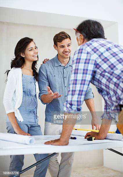 Young couple and architect discussing home renovation plan