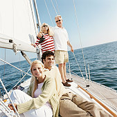 Young Couple and Mature Couple Sit and Stand on the Deck of a Sailboat Smiling