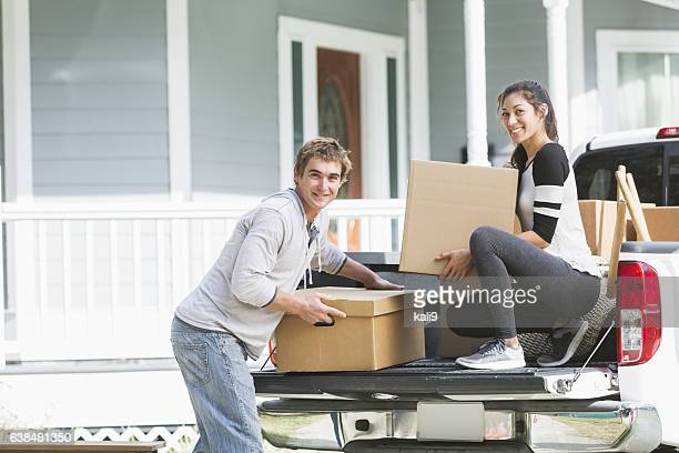 Young couple and pickup truck loaded with boxes and furniture
