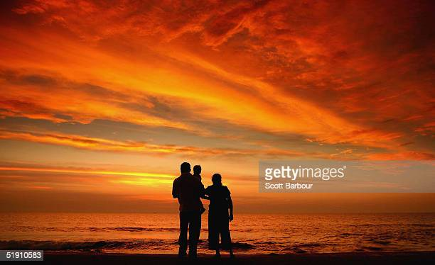 A young couple and their child look out to the sea at sunset as Sri Lankans try to resume their normal lives after the Indian Ocean tsunami disaster...