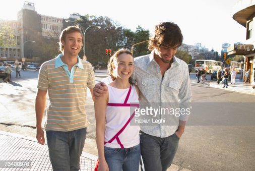 Young couple and young man walking by street outdoors, smiling : Stock Photo