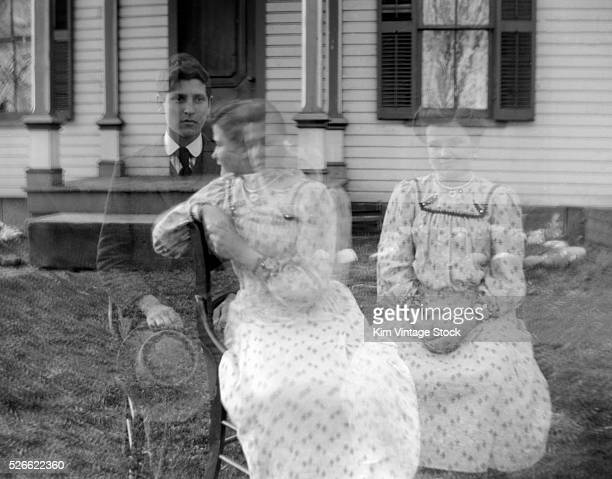 A young couple appear ghostlike in a double exposure photograph in the early 20th century