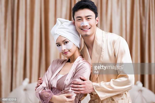 Young couple applying facial masks