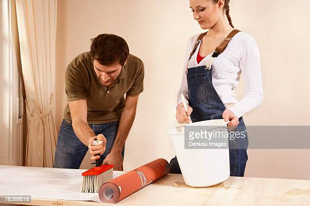 Young couple applying glue on wallpaper