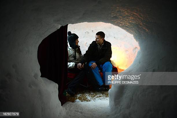 A young couple are about to sleep in an igloo on February 23 2013 in a village of igloos at the Le Semnoz village French Alps AFP PHOTO / PHILIPPE...