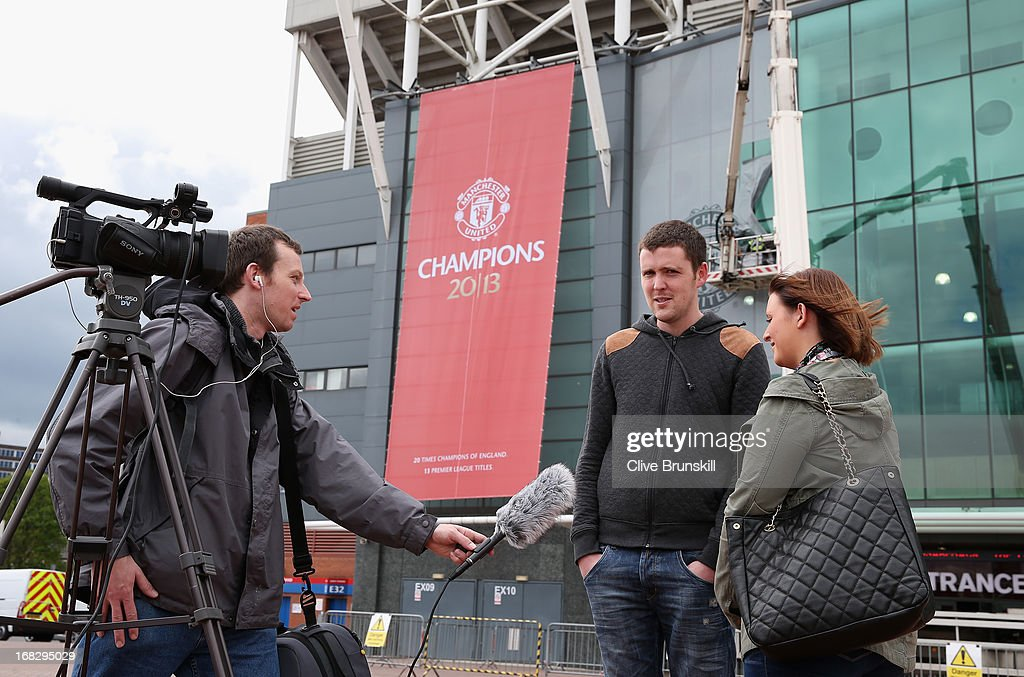A young couple are interviewed by the media outside the front of Old Trafford on the day Manchester United manager Sir Alex Ferguson announced his retirement as club manager on May 8, 2013 in Manchester, England.