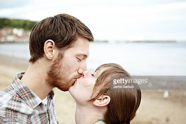 A young couple are kissing at the coast