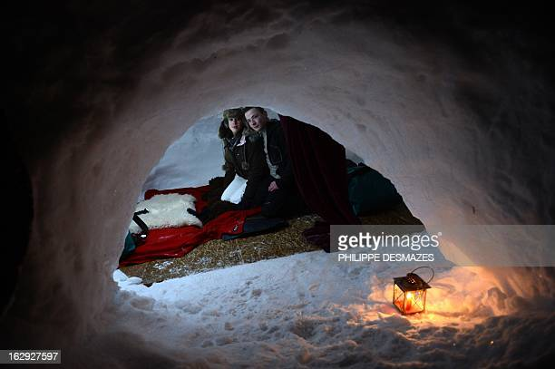 A young couple are pictured as they are about to sleep in an igloo on February 23 2013 in a village of igloos at the Le Semnoz village French Alps...