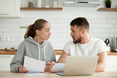 Young unhappy couple arguing about money bills documents at home kitchen, family disputing disagreeing on budget expenses, man and woman quarreling having financial problem with papers and laptop