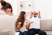 Young couple arguing during therapy session, man tired. Relationship problems, family issues concept