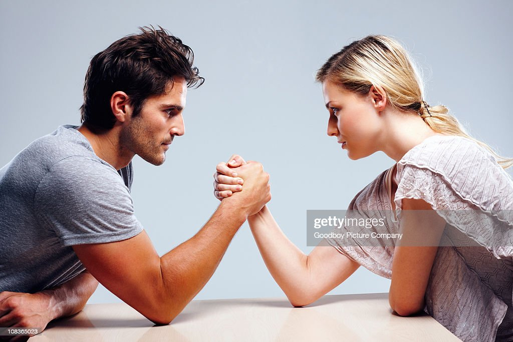 Young couple arm wrestling against grey background : Stock Photo