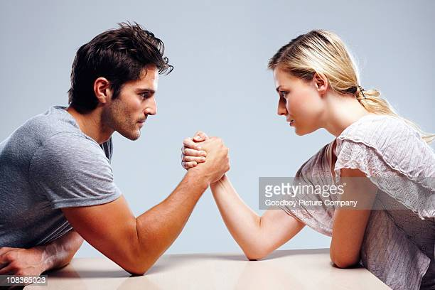 Young couple arm wrestling against grey background