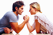 Young couple arm wrestling against white background