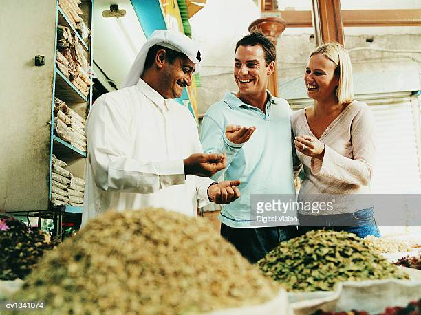 Young Couple Asking a Market Trader About Spices in a Sack at a Souk in Dubai
