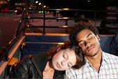 Young couple asleep on open top bus
