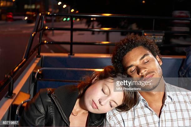 Jeune couple endormi sur bus à toit ouvert