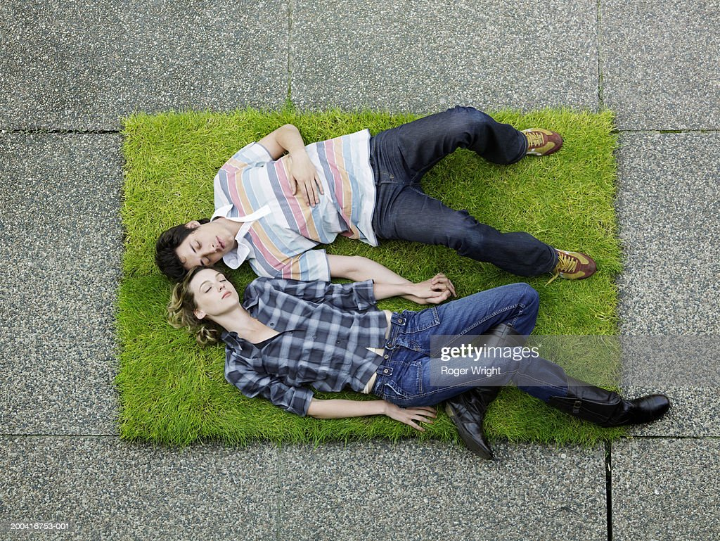 Young couple asleep on patch of turf, overhead view : Stock Photo