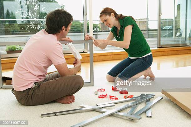 Young couple assembling flat-pack furniture, side view