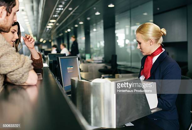 Young Couple At Airline Check-in Counter