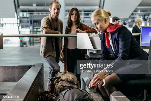 Young Couple At Airport Baggage Drop Off