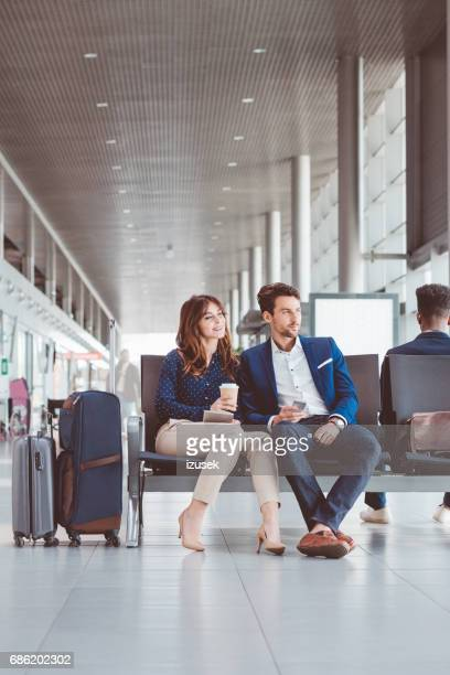 Young couple at airport departure area waiting for their flight