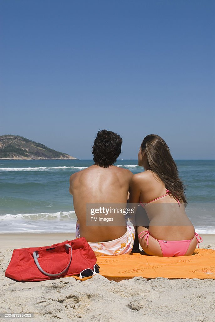 Young couple at beach facing sea, rear view : Stock Photo