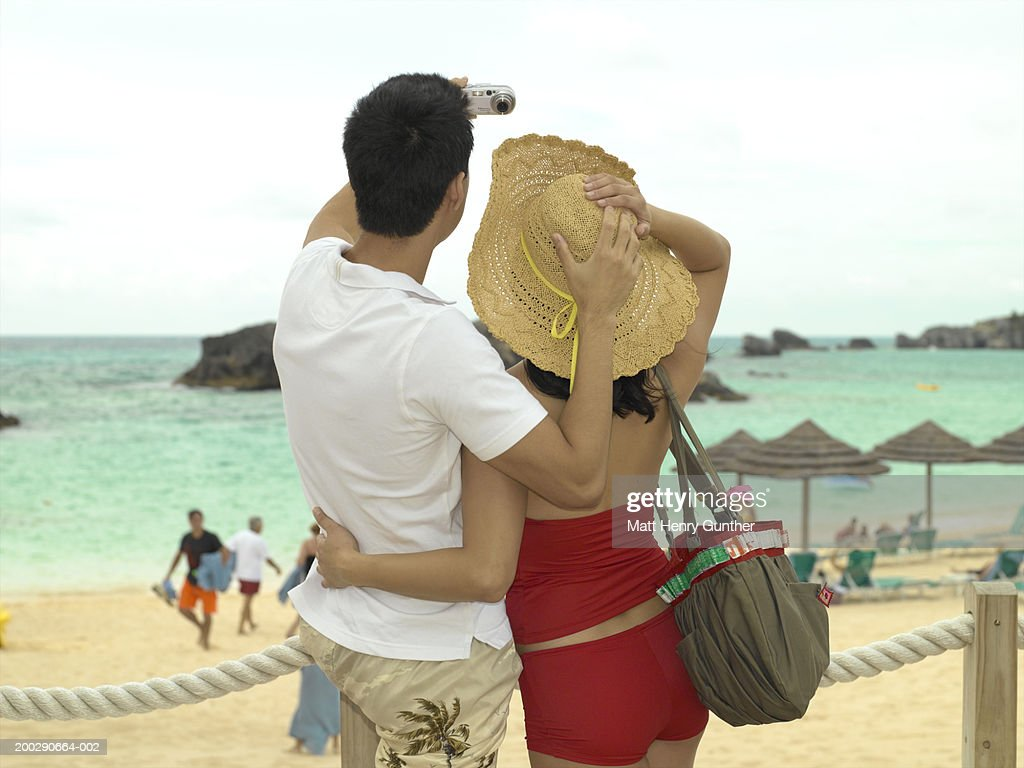Young couple at beach, man taking digital photo, rear view