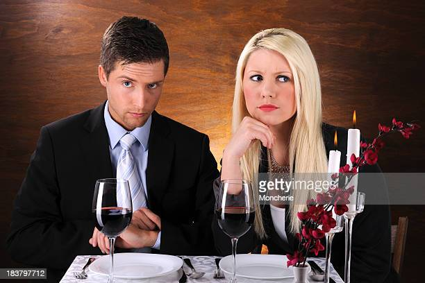 Young couple at dinner with negative expression
