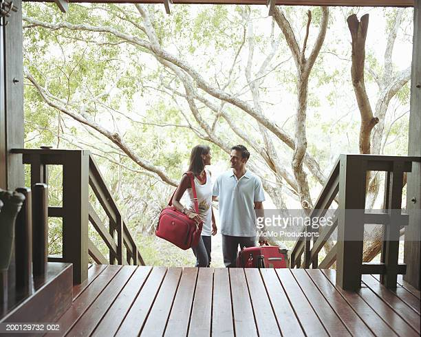 Young couple at foot of steps to lodge