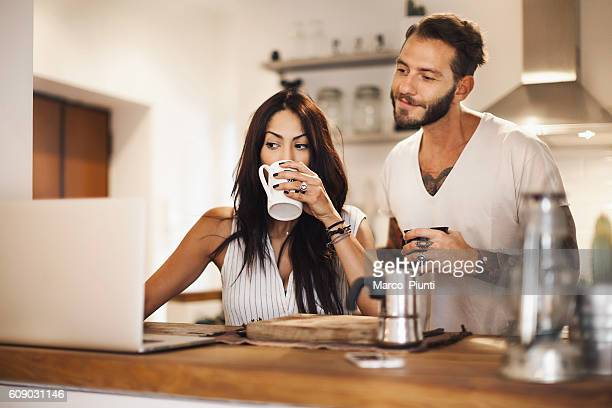 Young couple at home using laptop - Morning breakfast time