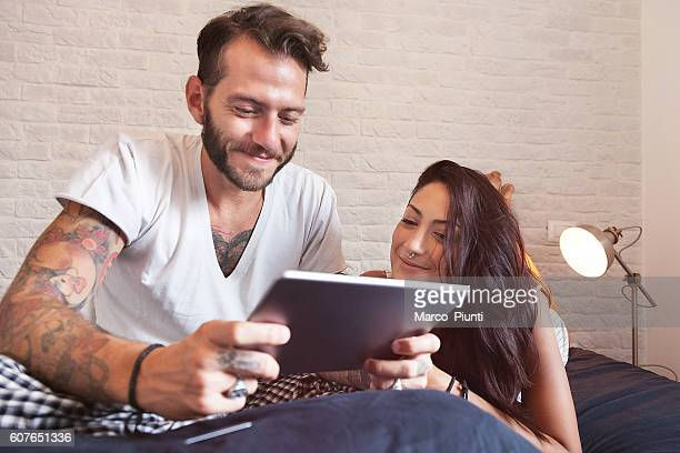 Young couple at home - Using tablet on the bed