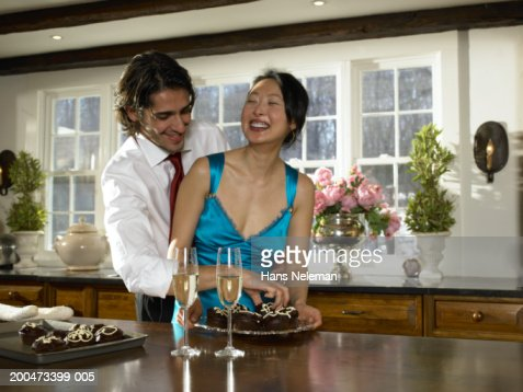 Young couple at party laughing, man reaching for cupcakes : Stock Photo