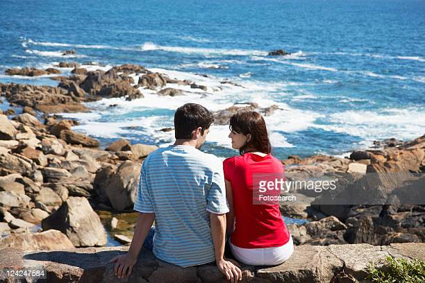Young couple at rocky beach (rear view)