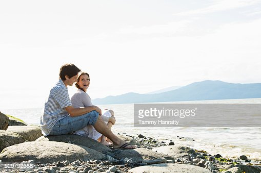 Young couple at sea relaxing on rock : ストックフォト