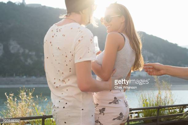 Young couple at waterfront roof terrace party, Budapest, Hungary