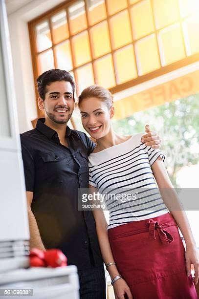 Young couple at work smiling at camera