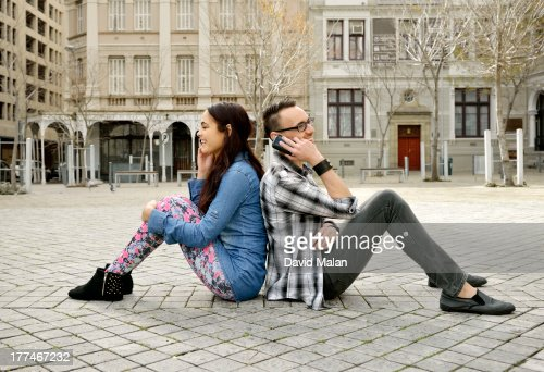young couple back to back talking on mobile phones