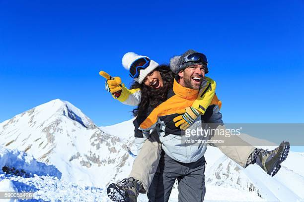 Young couple backpackers having fun in the snow mountain