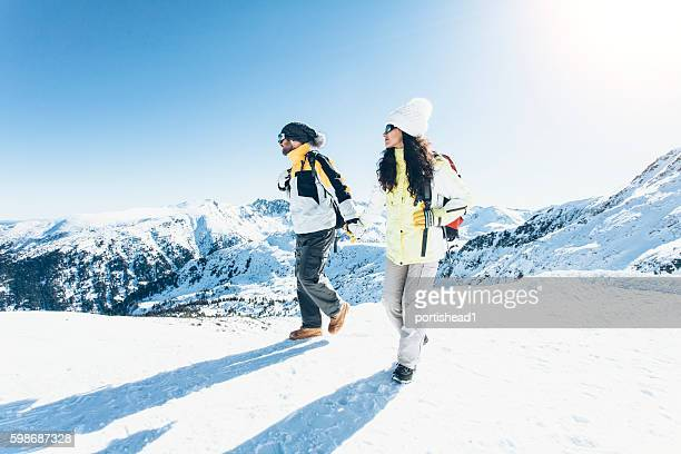 Young couple backpackers walking in the snow