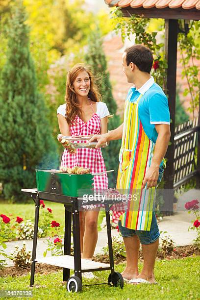 Young Couple Barbeque in a back yard.