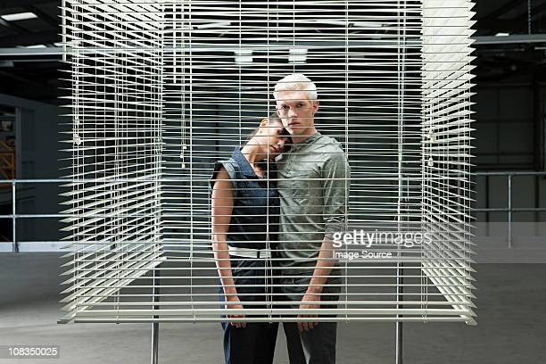 Young couple behind venetian blind, woman with head on man's shoulder