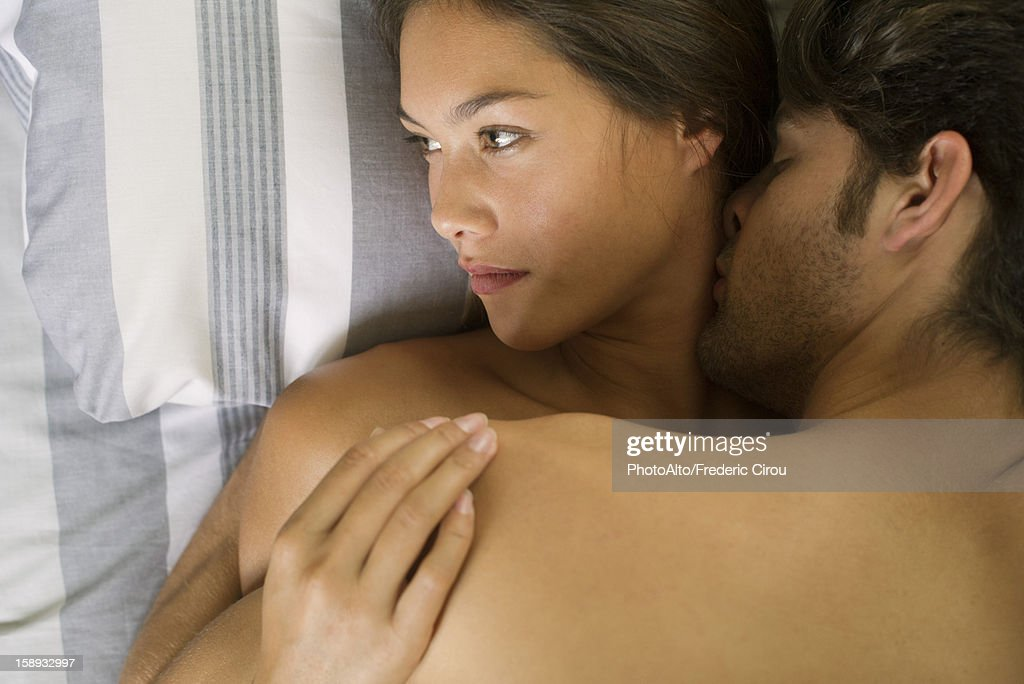 Young couple being intimate in bed, woman looking away : Stock Photo