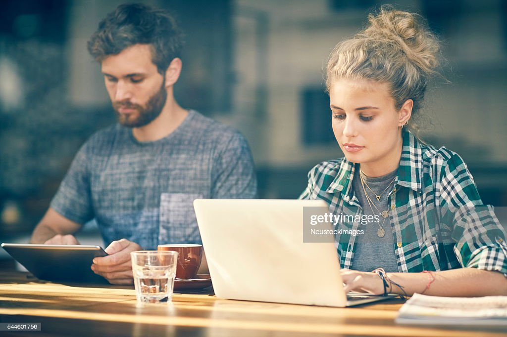 Young Couple Blogging On Tablet An Laptop Inside Cafe Window : Stock Photo