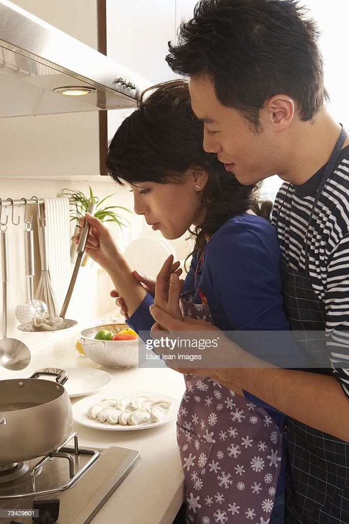 A young couple blow on a dumpling hot from the pot. : Stock Photo