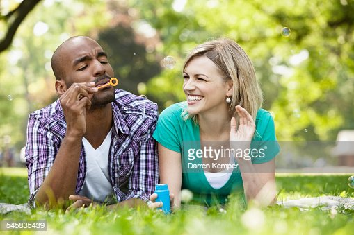 Young couple blowing bubbles in a park : Stockfoto